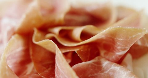 Macro of spinning thin slices of pork ham on the dish (close up)