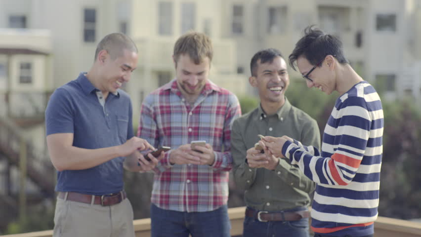 Group Of Happy Gay Friends Check Their Smart Phones And Share Photos With Each Other At A Rooftop Party In San Francisco (4K)
