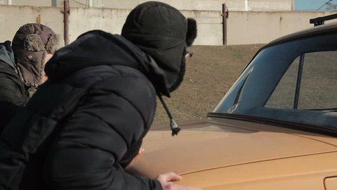 Men pushing broken down car at winter time. Woman sitting on the wheel