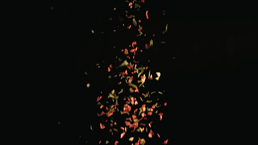 Slow motion shot of sprinkling colorful spices against a dark background
