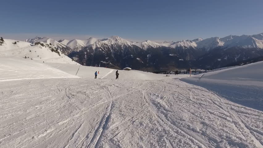 Bad Gastein, Austria, January 2018: Bad Gastein ski resort with snow-covered slopes in winter. Skiers and snowboarders ride on the prepared routes in the mountains. European Alps | Shutterstock HD Video #1006584604