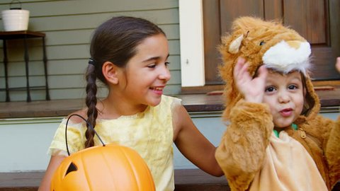 Children In Halloween Costumes For Trick Or Treating On Steps