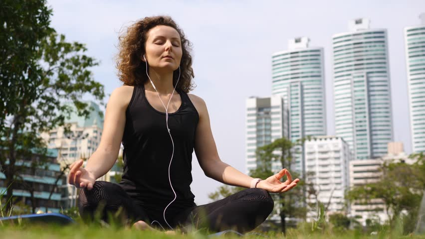 Young Woman In Earphones Doing Meditation In City Park. | Shutterstock HD Video #1006600234