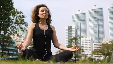 Young Woman In Earphones Doing Meditation In City Park.