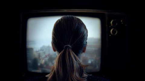 Watching Old TV Television Channels. Young woman watching old television in the dark. Shot behind model shoulders.