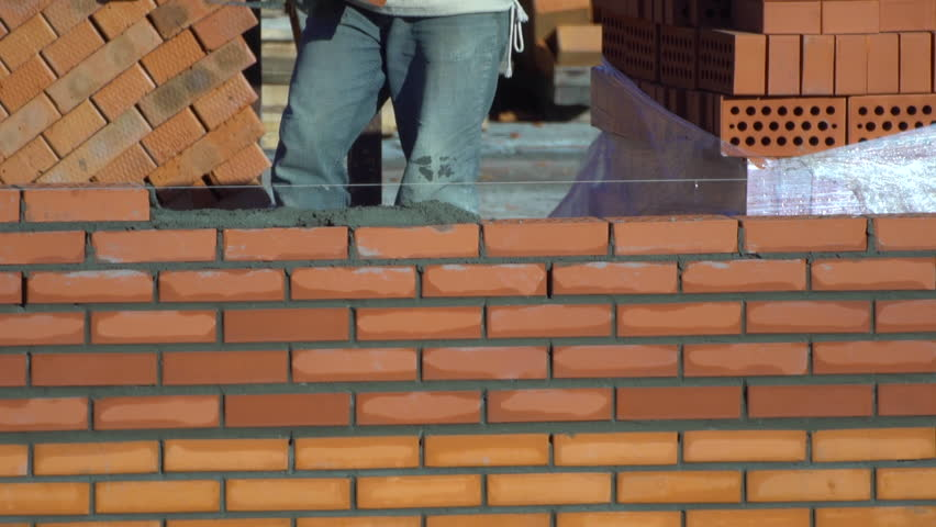 time lapse view of worker builds a wall of bricks in summer day. the builder on a building makes bricklaying. the builder at the construction site makes brickwork. construction? brick laying