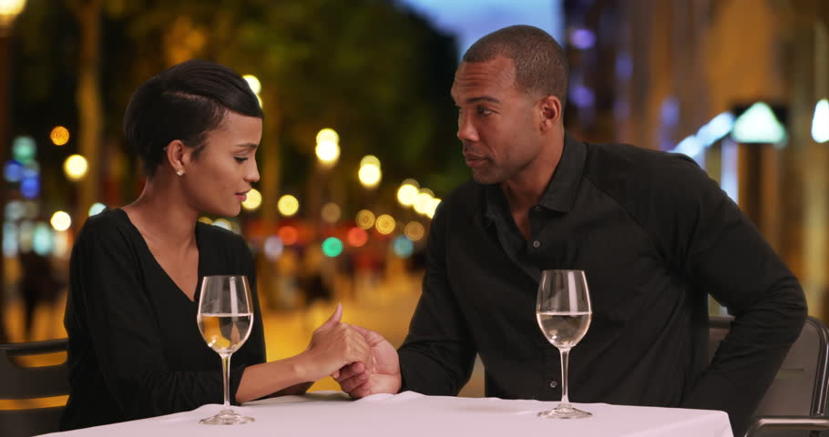 Loving black couple get engaged while out on a date at a nice restaurant. Loving young African male asks for his long time girlfriend's hand in marriage. 4k