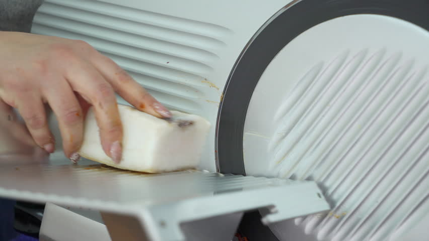 Electric food slicer. Chef slices salted lard. Professional slicing machine cutting processed meat products. Woman cuts pork lard closeup.