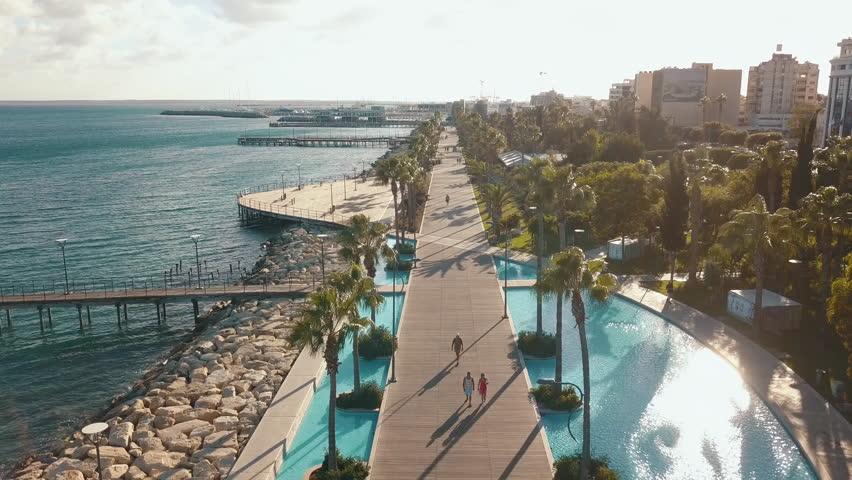 Aerial view of the coast of Limassol city in Cyprus. A view of the walk path surrounded by palm trees, pools of water, grass, the Mediterranean sea, piers, rocks and urban skyline.