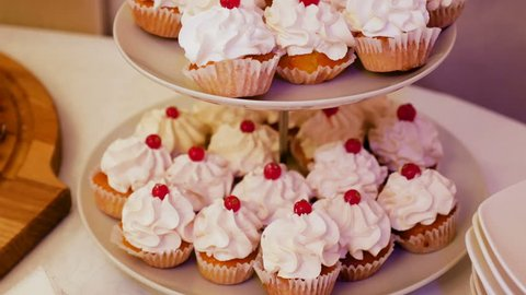 cap cake with cream and cherry on top are the bunk tray