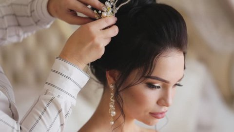 Stylist finishes a hairstyle the pretty young bride at wedding day in slow motion.