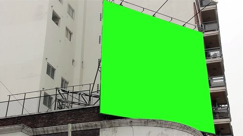 "Billboard with Green Screen on a Building. Ready to replace green screen with any footage or picture you want. You can do it with ""Keying"" (Chroma Key) effect with your video editing software."