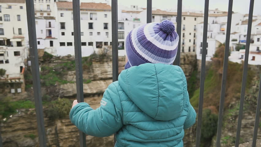 The kid in the old town. Running and looking through the trellis fence. The concept of freedom. Portraits. Spain. Ronda. shot with stedicam | Shutterstock HD Video #1006761334