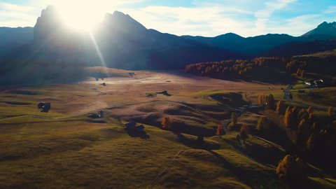 Aerial autumn sunrise scenery with yellow larches, alpine village and Odle - Geisler mountain group on background. Alpe di Siusi (Seiser Alm), Dolomite Alps, Italy