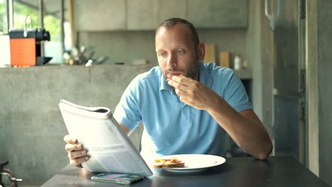 Young man reading magazine and eating breakfast by table in kitchen at home