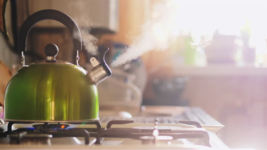 Boiling green kettle boiling with steam emitted from spout. The camera gently moves to the right. Solar glare from the kitchen window. Shallow depth of field #1006807924