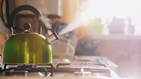 Boiling green kettle boiling with steam emitted from spout. The camera gently moves to the right. Solar glare from the kitchen window. Shallow depth of field