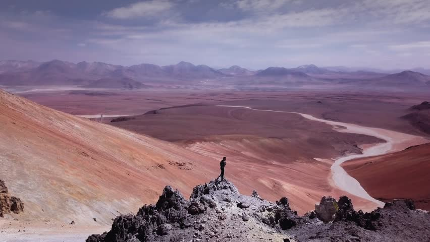 Male trail-runner on summit of the volcano Toco on Atacama desert, 4k. Aerial view of man contemplating the surroundings of volcano peak.