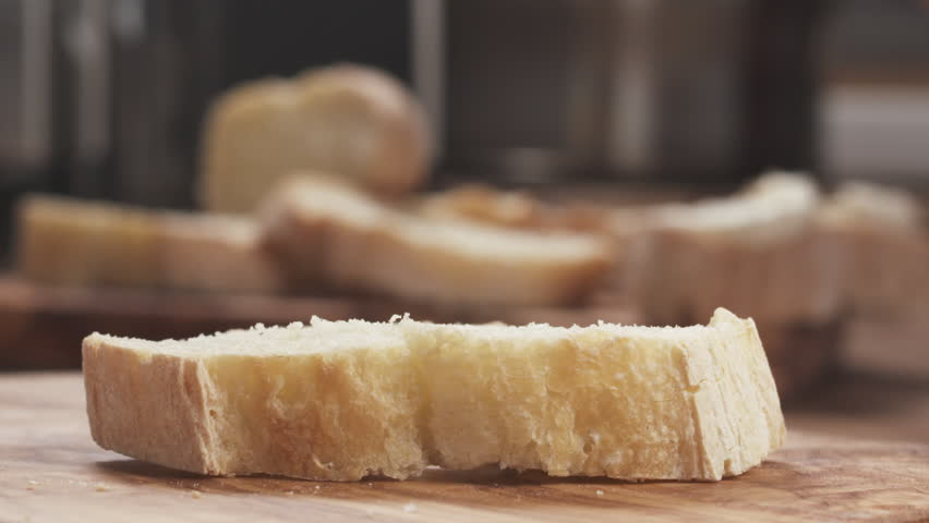Slow motion closeup of spreading cream cheese on fresh baguette slice