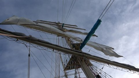 Square sail on the mast of a sailing tall ship rolling with the sky in the background
