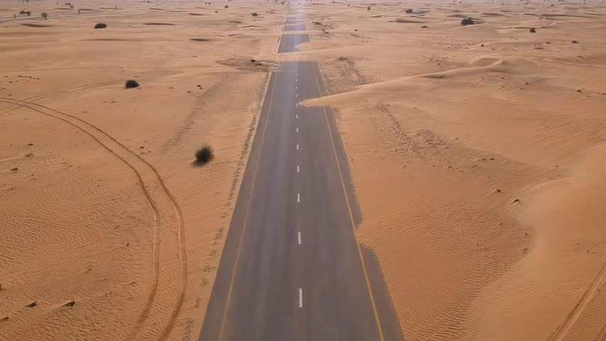 Dubai Flying with drone forward blocked road with sands in desert with drone footage Arabian desert in Dubai, United Arab Emirates, UAE.