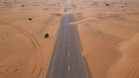 Flying with drone forward blocked road with sands in desert with drone footage Arabian desert in dubai UAE