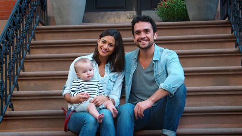 Young couple with a baby sitting on front stoop, close up