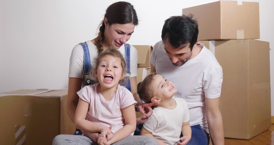 Portrait of a beautiful happy and smiling family holding the house shaped meter just arrived in the new house to start a new path together. Concept of: love, family, home. | Shutterstock HD Video #1006877884