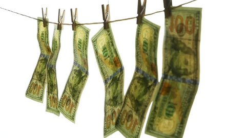 Dollar banknotes hang on a rope with clothespins. The concept of dirty money.