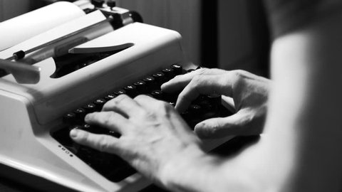 Hands typing a film script or a book on a vintage typewriter, 4k black and white video