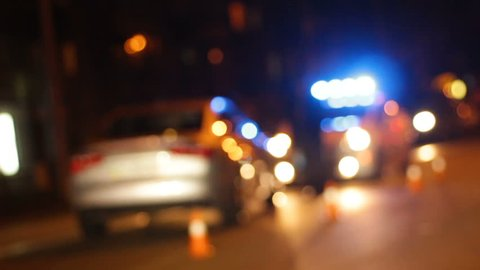 Patrol car arriving at scene of road accident, cars driving night city street