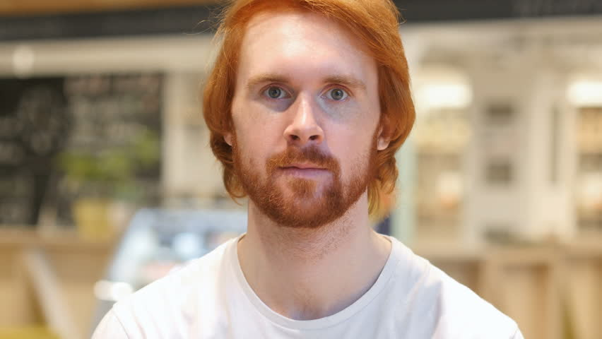 Serious Redhead Beard Man Looking at Camera in Cafe #1006967464
