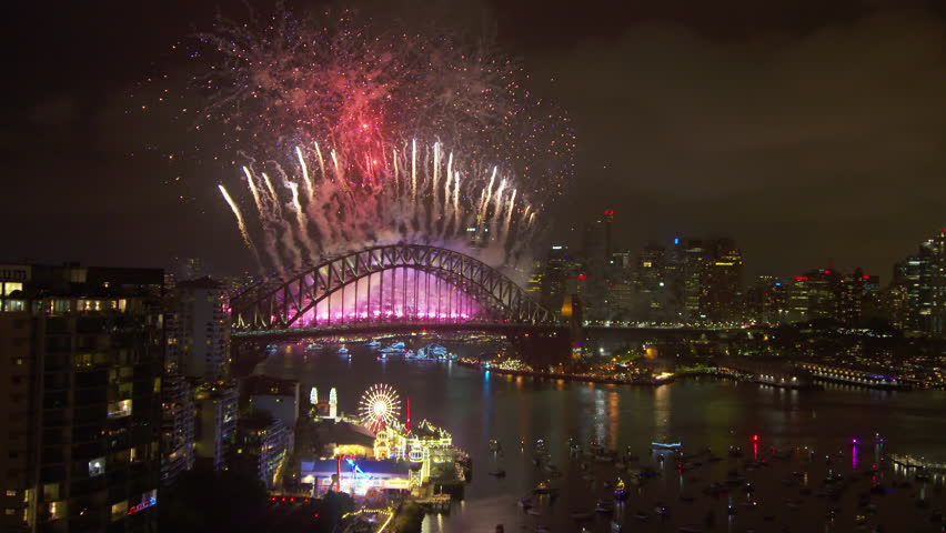 A steady long shot of the harbour bridge as a colourful and majestic fireworks blew up behind it. #1006991314