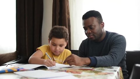 Mixed family at home. African father and african american child. dad helping son with school homework. Education and relationship, man teaching and boy learning. home schooling.