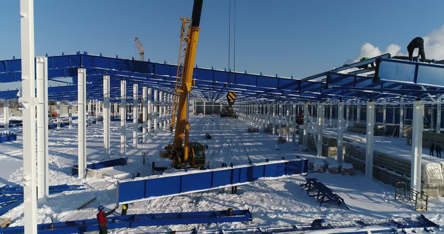 The building crane lifts the metal beam, industrial exterior, Construction of a modern factory or plant, the structural steel structure of a new commercial building, assembly of metal structures | Shutterstock HD Video #1007009374