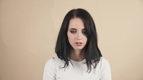 a young beautiful cute brunette on a beige orange background showing sarcasm, surprise emotions