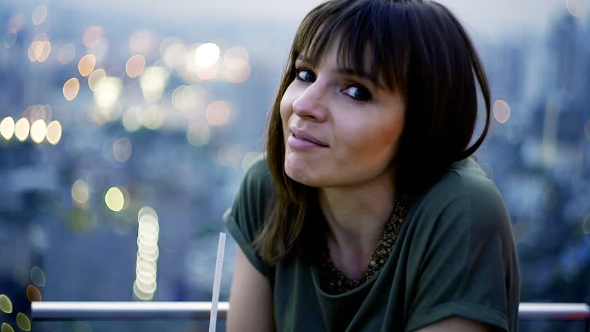 Happy woman talking to camera, sitting at rooftop bar | Shutterstock HD Video #1007023534