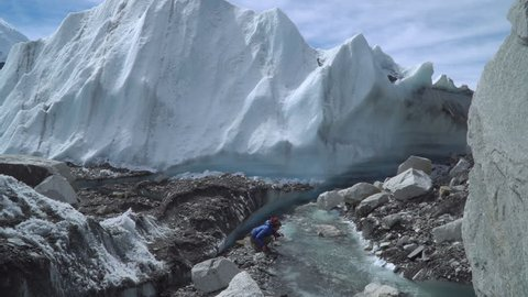 The Khumbu Glacier descends from Mount Everest. Walking on the glacier is very dangerous. A girl drinks water from a creek. Nepal. Himalayas. 4K