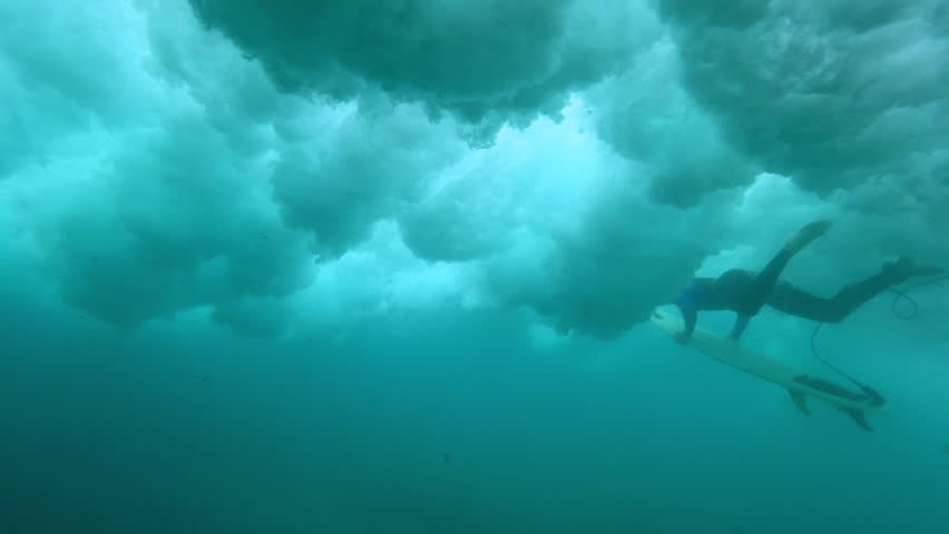 UNDERWATER, SLOW MOTION: Brave male surfer paddling in deep water as wild waves crash above him. Extreme sportsman doing a duck dive in ocean. Awesome underwater shot of intimidating waves breaking.