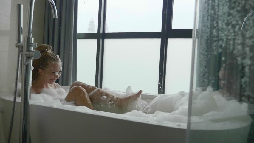 Beautiful woman relaxing in bubble bath lying in bathtub. Beauty care, leisure activity and healthcare concept. | Shutterstock HD Video #1007097664