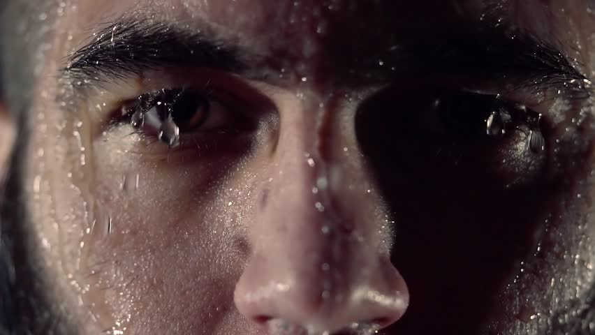 close up shot of the face of a dark-bearded man who stands in the rain in the studio