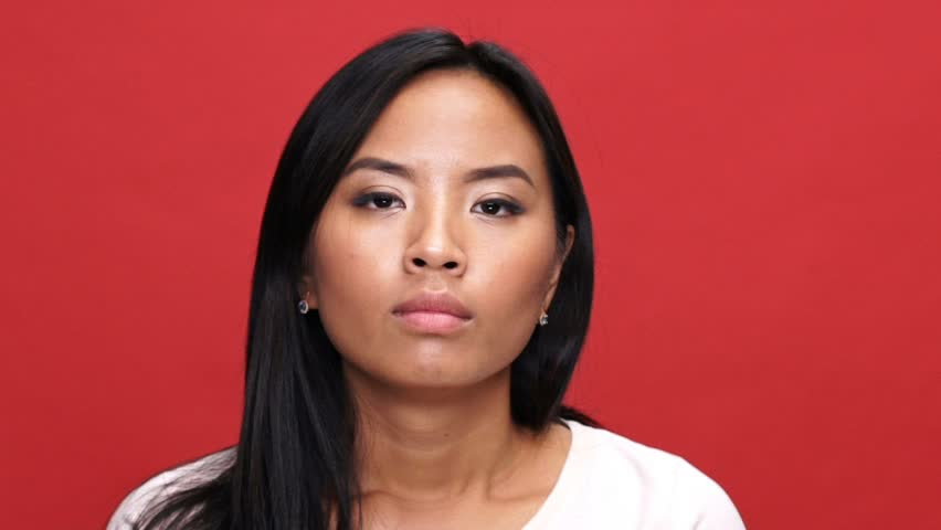 Close up view of confused asian woman in t-shirt disagrees with something and looking around over red background | Shutterstock HD Video #1007141614
