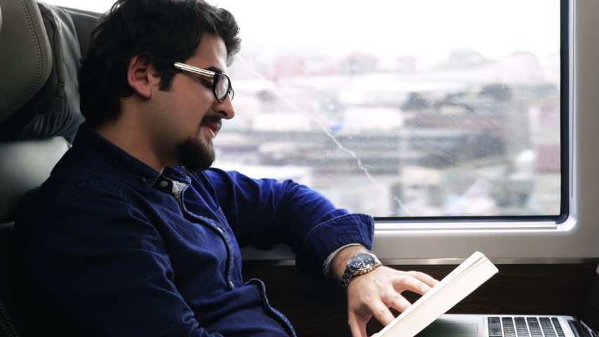 A man reads a book while traveling on a train | Shutterstock HD Video #1007147254