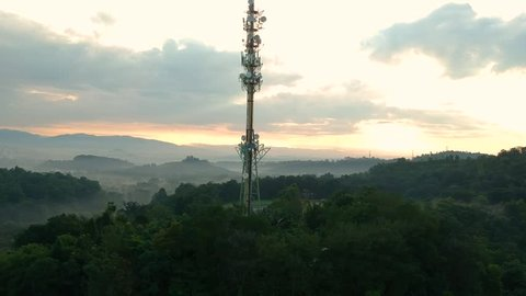 Aerial footage of Communication tower during morning sunrise with clouds, mists and fog