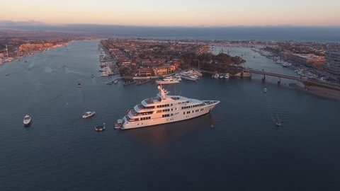 Aerial orbit view of luxury super yacht or mega-yacht docked in harbor