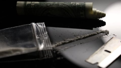 Close up of cocaine razor blade and dollar bill. Illegal drug use on a black shiny table. Drug trafficking and abuse concept close up.