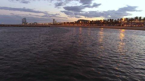Nightlife on beach in Barcelona, Spain, aerial view, birds following drone
