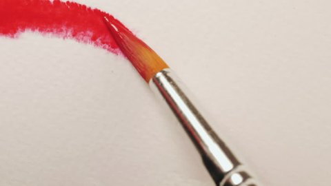 Paintbrush moves across canvas leaving red brush strokes of paint.
