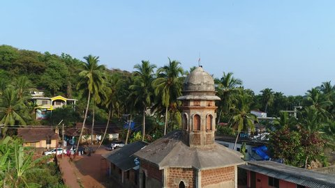A small Hindu temple in a village on the shore of the bay and several fishing dinghies near it. Aerial view.