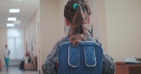 A little girl in a jacket and with a funny backpack stands with her back in the corridor lobby  of the clinic, a doctor comes towards her